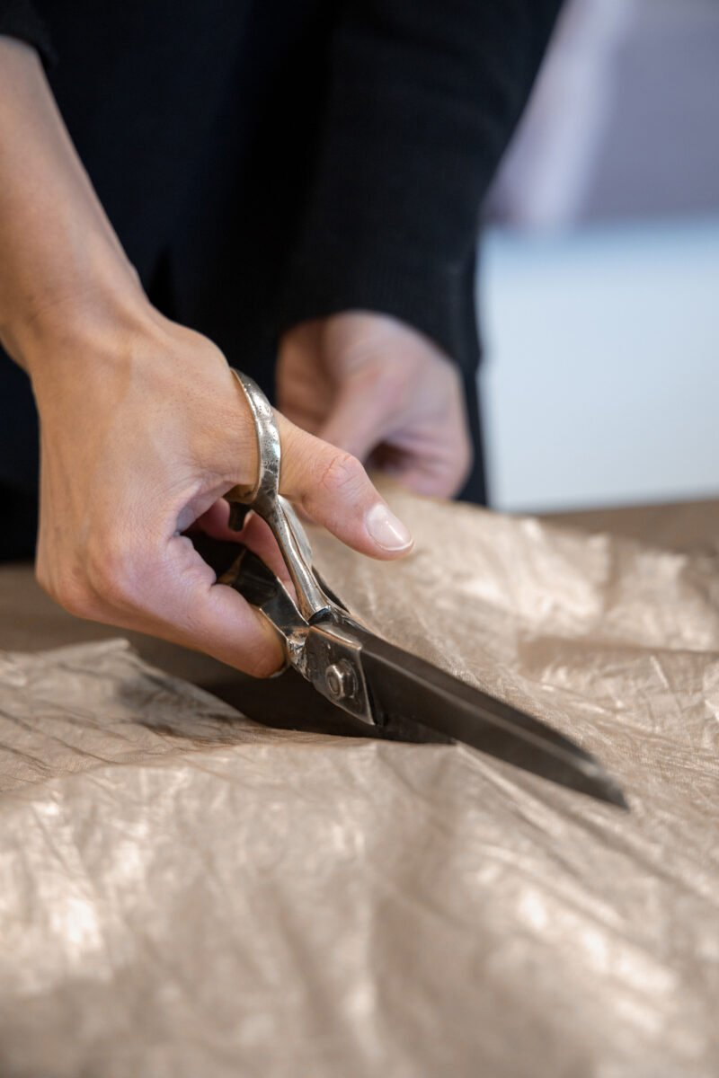 cutting gold cotton with large scissors